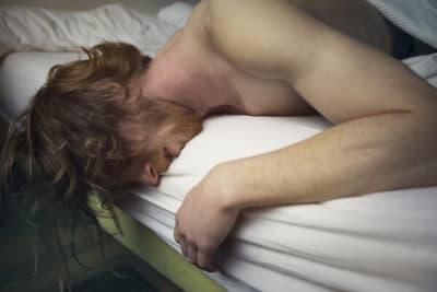 Homme penché sur son lit en proie au sevrage médicamenteux