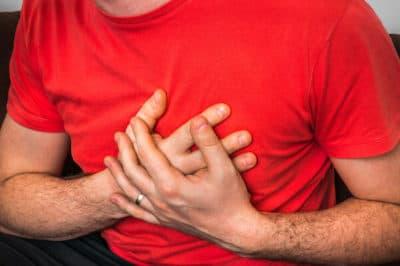 Mężczyzna trzymający ręce przy klatce piersiowej doświadcza arytmii